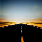 Vibrant image of highway and blue sky. In motion blur Stock Photos