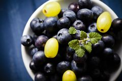 Blueberries and grapes on white bowl royalty free stock photo