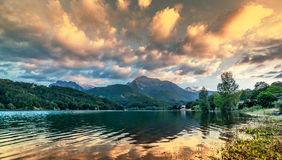 Vibrant intense sunset landscape on lake and mountain background Stock Photos