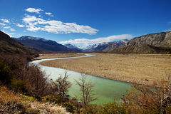 Vibrant Landscape with Emerald River and Mountains. Beautiful landscape of a valley with a winding, green river and trees in the foreground. Image was taken int stock image