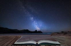 Vibrant Milky Way composite image over landscape of yellow sandy beach Three Cliffs bay coming out of pages in magical story book. Stunning vibrant Milky Way royalty free stock photos