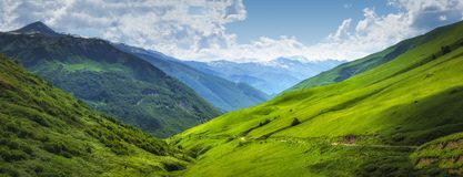 Vibrant mountain landscape. Green meadows on the high hills in Georgia, Svaneti region. Panoramic view on grassy highlands stock photography
