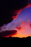Vibrant Mountain Sunset. Beautiful Vibrant Sunset with oranges, purples and yellows filling the intense background sky over the Silhouette of a mountain Range stock image