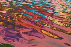 Vibrant multi colored ripples and waves of water with shades of pink, red, orange and lavender, background, abstract stock images