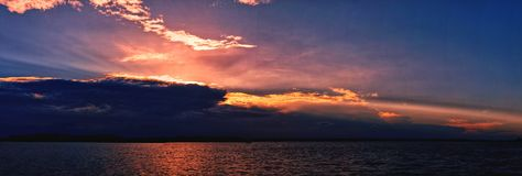 Vibrant ocean sunset seascape through cloud and with water refle Stock Photos