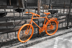 Vibrant orange bicycle on the gray background Royalty Free Stock Image
