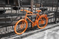 Vibrant orange bicycle on the gray background Royalty Free Stock Image