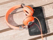 Vibrant orange headphones and black tablet pc on wooden bench Royalty Free Stock Image