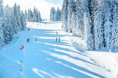 Vibrant panorama of the slopes at ski resort, snow trees, blue sky. Vibrant panorama of the slope at ski resort, snow pine trees, blue sky Royalty Free Stock Photo