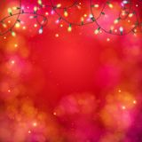 Vibrant party background with a garland of lights. Vibrant red abstract party background with a garland of multicolored lights in a twirled pattern at the top Stock Image