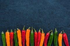 Vibrant peppers on dark slate Stock Photography