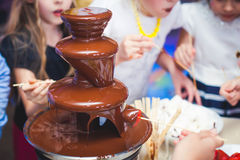 Vibrant Picture of Chocolate Fountain Fontain on childen kids birthday party with a kids playing around and marshmallows and fruit. S dip dipping into fountain Stock Images
