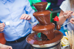 Vibrant Picture of Chocolate Fountain Fontain on childen kids birthday party with a kids playing around and marshmallows and fruit. S dip dipping into fountain Stock Photography