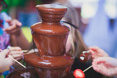 Vibrant Picture of Chocolate Fountain Fontain on childen kids birthday party with a kids playing around and marshmallows and fruit. S dip dipping into fountain Royalty Free Stock Photo