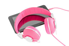 Vibrant pink female headphones and black tablet pc Royalty Free Stock Photos