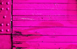 Vibrant pink wood and metal background texture. With old stained weathered wooden boards and a metal corner plate with studs Stock Photo