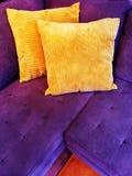 Vibrant purple sofa with orange cushions stock image