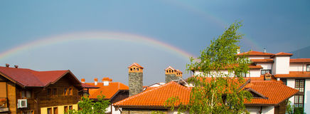 Vibrant Rainbow behind the roofs and trees Stock Images