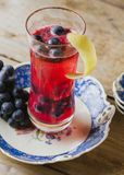 Cranberry color cocktail garnished with fresh grapes on a vinta. Vibrant red alcoholic beverage in a tall glass on rustic background royalty free stock photos