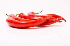 Vibrant red chillis. Three vibrant red chillis on a backdrop of dark slate royalty free stock photos