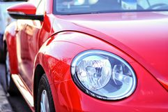 Vibrant red colour car side view and detailed car light. Modern. Design of the sport and elegance look Royalty Free Stock Photos