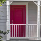 Vibrant red front door and balcony of a home. Home with vibrant red front door and horizontal white panels on the exterior wall. White railing and slim carved royalty free stock images