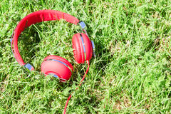 Vibrant red headphones on fresh glade Stock Image