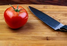 A vibrant ripe red beef steak tomatoon a cutting board with a ch stock photography