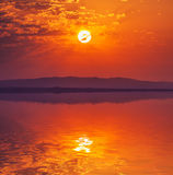Vibrant rising sun at dawn over water Stock Image