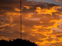 Vibrant, rougeoyant, le nuage a rempli lever de soleil étant soulevé au-dessus d'un premier plan de silhouette images stock