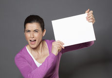 Vibrant 30s woman making an announcement in raising a white insert in front of her Royalty Free Stock Image