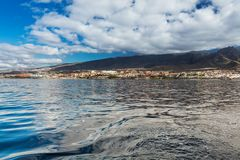 Vibrant scenery and deep-blue waters of the Tenerife west coastline as seen from a yacht. The dormant Teide volcano can be seen in. The background. Many tourism royalty free stock photos