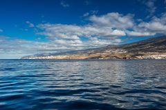 Vibrant scenery and deep-blue waters of the Tenerife west coastline as seen from a yacht. The dormant Teide volcano can be seen in. The background. Many tourism stock images