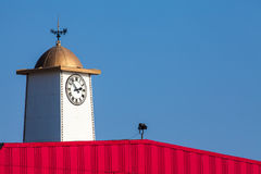 Vibrant seaside pier clock tower with weathervane. Stock Photos