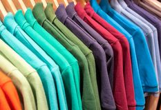 6123bbba069 Vibrant shirts on hangs for sale in shop. Multicolored polo on wooden  hanger. Summer