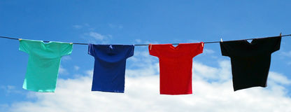 Vibrant Shirts on a Line. Bright colorful shirts hang on a line in front of a brilliant blue sky. The shirts are mint green, royal blue, red and black Stock Photo