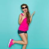 Vibrant Shouting Woman. Shouting young woman in sunglasses, pink shirt, jeans shorts, and pink sneakers posing on one leg. Three quarter length studio shot on Stock Photography