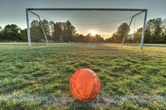Vibrant soccer ball centered in front of soccer goal at sunrise. With a sun flare Royalty Free Stock Image