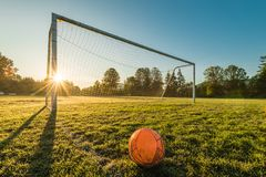 Vibrant soccer ball off centered in front of soccer goal at sunr. Ise with a sun flare Stock Images
