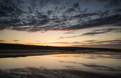 Vibrant sunrise landscape reflected in low tide water on beach Royalty Free Stock Photo