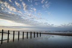 Vibrant sunrise landscape reflected in low tide water on beach Stock Photography