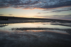 Vibrant sunrise landscape reflected in low tide water on beach Royalty Free Stock Photography
