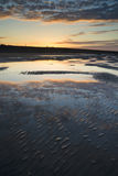 Vibrant sunrise landscape reflected in low tide water on beach Stock Images