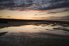 Vibrant sunrise landscape reflected in low tide water on beach Stock Photos