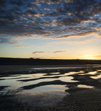 Vibrant sunrise landscape reflected in low tide water on beach Stock Photo