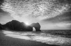 Vibrant sunrise over ocean with rock stack in foreground in blac. Winter sunrise behind Durdle Door on Jurassic Coast in black and white Royalty Free Stock Photography