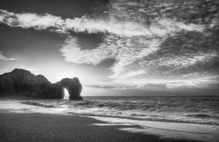 Vibrant sunrise over ocean with rock stack in foreground in blac. Winter sunrise behind Durdle Door on Jurassic Coast in black and white Stock Images