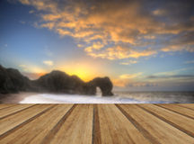 Vibrant sunrise over ocean with rock stack in foreground with wo Stock Photos