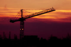 Vibrant sunset with crane silhouette in frame Stock Images