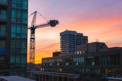 Free Vibrant Sunset Illuminating Clouds Over High Rise Apartment Buildings And A Crane. Toronto Canada Stock Images - 214566954